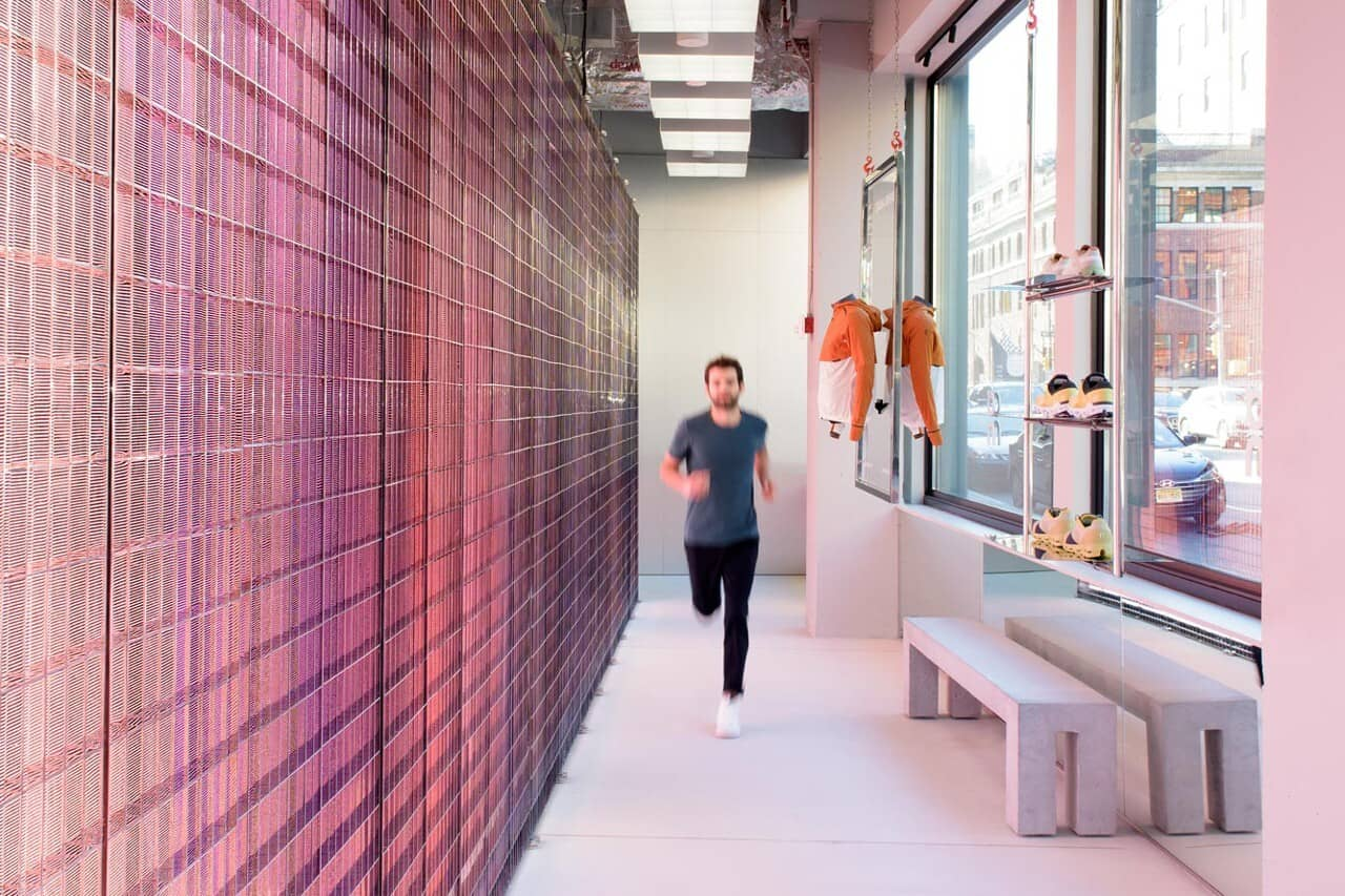 A man jogs towards camera inside ON Experience Store NYC, with the 62 foot long magic wall to his left